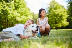 Barnet kramar hunden med affektion royaltyfri foto
