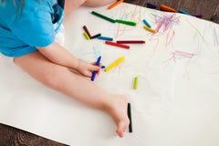 Barnet lär att dra vaxfärgpennor, sitter på golvet arkivbilder