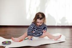 Barnet lär att dra vaxfärgpennor, sitter på golvet royaltyfri bild