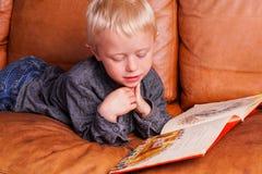 Barnet läser in en bok royaltyfri foto