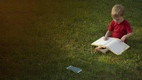 Barnet läser en bok, medan att sitta på gräset och hans mobiltelefonlögner bredvid den vände av Begreppet av utbildning och royaltyfri fotografi