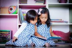 Barnet läste, läseboken för två den gulliga små flickor tillsammans på böcker Arkivbilder