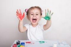 Barnet l?mnar hennes handprints p? papper royaltyfria bilder