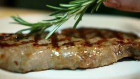 Barnet lagar mat sätter rosmarinfilialer på stekt kött i kök av restaurangen stock video
