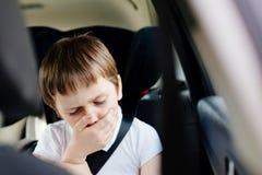 Barnet lider från rörelsesjukdom i bil Arkivbild