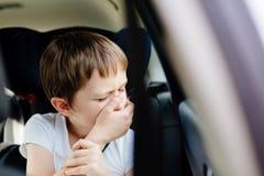 Barnet lider från rörelsesjukdom i bil Royaltyfri Fotografi