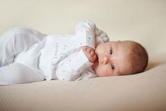 Barnet ligger på den ljusa plädet i vit pyjamas Fotografering för Bildbyråer