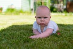 Barnet ligger på gräset i trädgården och rynkar pannan Arkivbild