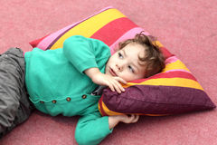 Barnet ligger på matta Arkivbild