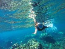 Barnet lossar hårkvinnan som snorklar i blåttmaskering i korallrev arkivfoton