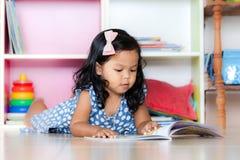 Barnet läste, den gulliga lilla flickan som läser en bok och ligger på golv Royaltyfri Bild