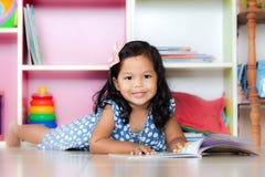 Barnet läste, den gulliga lilla flickan som läser en bok och ligger på golv Royaltyfria Foton