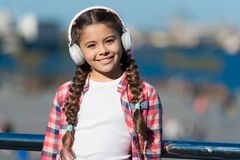 Barnet lyssnar modern hörlurar för musik utomhus Ungeliten flicka att lyssna sånghörlurar Musikkontoplaylisten skräddarsy arkivbild