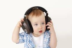 Barnet lyssnar till musik i stor hörlurar royaltyfri fotografi