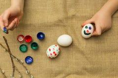 Barnet målar ägg för påsk stock illustrationer