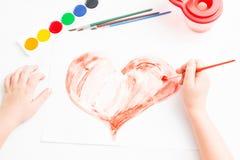 Barnet målar en röd hjärta Arkivbild