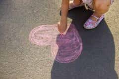 Barnet målar krita på asfalthjärtan Selektivt fokusera royaltyfria bilder