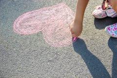 Barnet målar krita på asfalthjärtan Selektivt fokusera royaltyfri bild