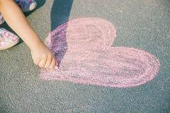 Barnet målar krita på asfalthjärtan Selektivt fokusera arkivfoto