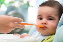 barnet matar den små mumen Royaltyfria Foton
