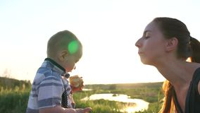 Barnet matar modern ett stycke av kakan, och hon kysser honom, ultrarapid stock video