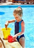 Barnet med ösregnar i simbassäng. Arkivbild