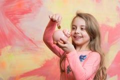 Barnet med den lyckliga framsidan sparar pengar för framtid Royaltyfri Fotografi