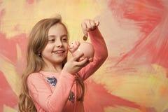 Barnet med den lyckliga framsidan sparar pengar för framtid royaltyfri bild