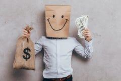 barnet med den pappers- påsen på head kassa och pengar hänger löst arkivbilder
