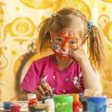 Barnet med en framsida målade med färgrika målarfärger (fyrkantserier) Royaltyfria Foton