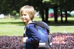 Barnet med en ryggsäck går till skolan Staden parkerar bakgrund Arkivbild
