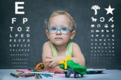 Barnet med exponeringsglas sitter på en tabell på bakgrunden av tabellen för en ögonundersökning Royaltyfri Fotografi