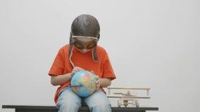 Barnet med flygarelockblick på jordjordklotjord som finner nya ställen för affärsföretag, makten av fantasi, kan du gå någonstans arkivfilmer