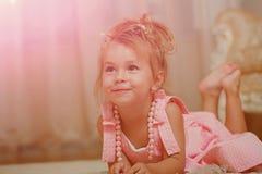 Barnet med gulligt leende i rosa färger klär lögn på matta royaltyfri fotografi
