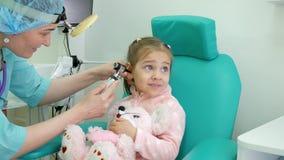 Barnet med leksaken i hans armar på mottagandet för doktors` s, det medicinska tillvägagångssättet, otolaryngologist behandlar sp arkivfilmer