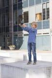 Barnet med ringer Pojke som ser skärmen och att spela lekar, genom att använda apps utomhus- Fritid för skolafolkteknologi Royaltyfria Bilder