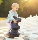 Barnet med schack figurerar utomhus- Royaltyfria Foton