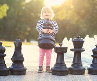 Barnet med schack figurerar utomhus- Arkivbild