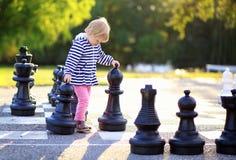 Barnet med schack figurerar utomhus- Arkivfoto