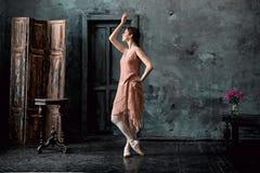 Barnet och den incredibly härliga ballerina är posera och dansa i en svart studio Royaltyfri Foto