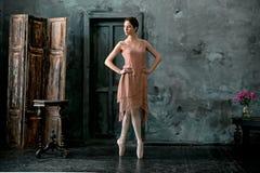 Barnet och den incredibly härliga ballerina är posera och dansa i en svart studio Arkivfoton