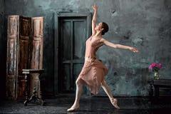 Barnet och den incredibly härliga ballerina är posera och dansa i en svart studio Royaltyfri Fotografi