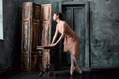 Barnet och den incredibly härliga ballerina är posera och dansa i en svart studio Arkivfoto
