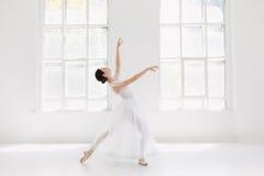 Barnet och den incredibly härliga ballerina är posera och dansa i en vit studio Arkivfoton