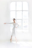 Barnet och den incredibly härliga ballerina är posera och dansa i en vit studio Royaltyfri Foto