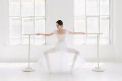 Barnet och den incredibly härliga ballerina är posera och dansa i en vit studio Arkivbild