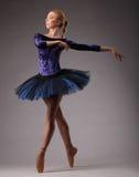 Barnet och den incredibly härliga ballerina i blåttdräkt är posera och dansa i studio klassiskt Arkivbild