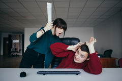 Barnet och den mycket onda flickakontorsarbetaren skriker på hans personal och önskar att slå dess säkerheter Arkivfoto