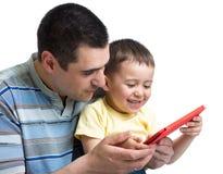 Barnet och farsan spelar och läser minnestavladatoren Royaltyfri Fotografi