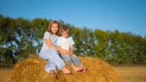 Barnet och flickan sitter på höstacken Royaltyfri Bild